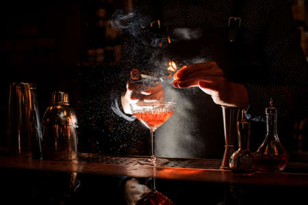 Bartender in black apron and blue shirt setting fire to sweet cocktail in bocal at a bar counter Stock Photo