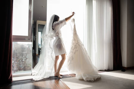 Pretty Brunette Bride In Silk Dressing Gown And Lacy Veil Holding ...