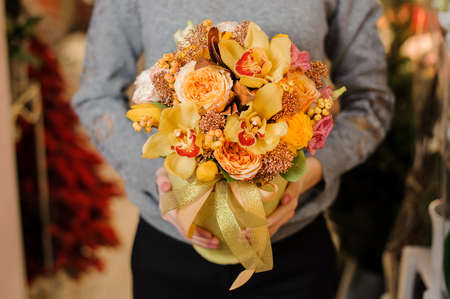 female in gray sweater holds a bouquet with orange irises and pion-shaped roses in golden packing with ribbon
