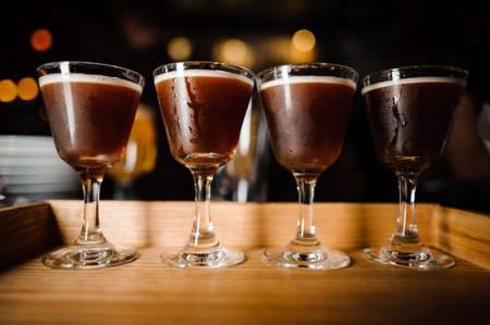 four chilled crystal glasses with chocolate-colored alcoholic cocktails and white foam stand on the bar counter