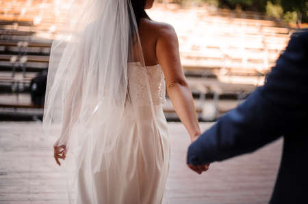 Groom following his beautiful bride dressed in a white wedding dress and veil holding her hand Standard-Bild