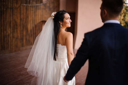 Groom in a blue suit following his beautiful smiling bride dressed in a white wedding dress and veil holding her hand. Back view