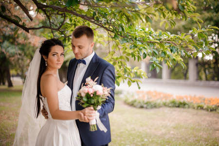 Happy and young married couple standing under the tree with a beautiful bouquet of flowers