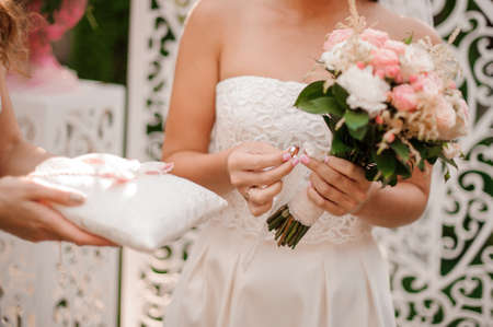 Bride dressed in a beautiful white wedding dress holding a golden wedding ring and bouquet of flowers