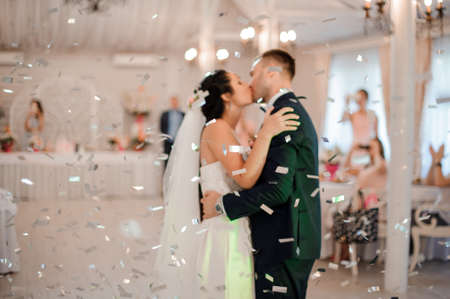 Young and happy married couple kissing in the centre of the elegant restaurant hall among falling confetti