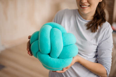 Woman in a grey shirt holding a cute blue knot pillow on the indoors background Standard-Bild