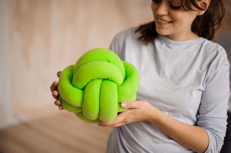 Woman in a grey shirt holding a cute green knot pillow on the indoors background