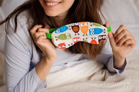 Young smiling woman holding a cute sleep mask with the owl print on the background of a white bed Standard-Bild