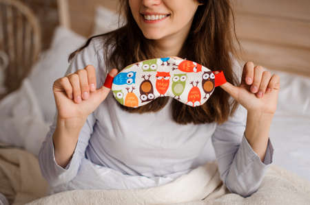 Young smiling girl holding a cute sleep mask with the owl print on the background of a white bed Standard-Bild