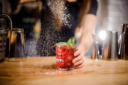 elegant barmaid finishes preparation of red alcoholic cocktail in crystal glass by adding a bitter of powdered sugar