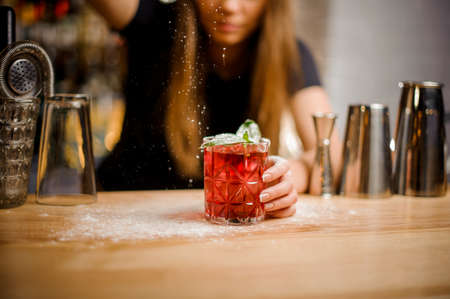 professional barista finishes preparation of pink alcoholic cocktail with mint leaves in crystal glass by adding a bitter of powdered sugar Standard-Bild