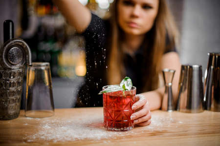 pretty professional barista finishes preparation of pink alcoholic cocktail with mint leaves by adding a bitter of powdered sugar