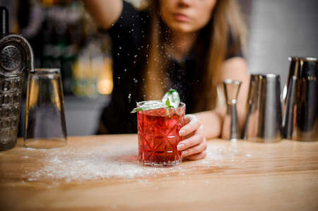 cute barista finishes preparation of red alcoholic cocktail with mint leaves by adding a bitter of powdered sugar