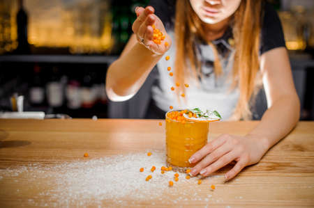 barmaid finishes preparation of alcoholic cocktail decorated with mint and dried orange by adding a bitter of sea buckthorn