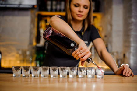 beautiful barmaid pours brightly crimson alcohol from a bottle into crystal stacks that are lined up