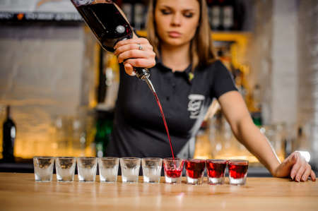 professional barmaid pours brightly crimson alcohol from a bottle into crystal stacks that are lined up