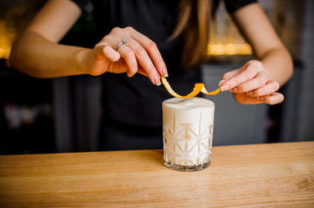 stylish barista holds orange peel over a crystal glass with an alcoholic cocktail and white foam