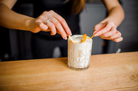 professional barmaid puts orange peel into a crystal glass with an alcoholic cocktail and white foam
