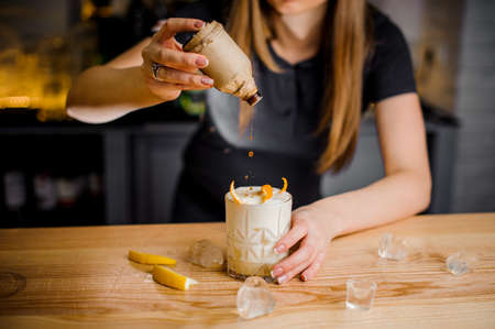 barista adds a topper to a white cocktail with orange peel surrounded by ice and lemon slices on the bar counter