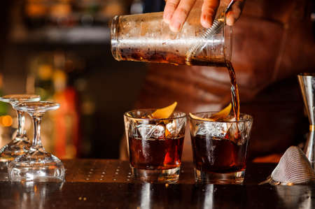 Bartender pouring fresh alcoholic drink into the glasses with ice cubes on the bar counter Stockfoto