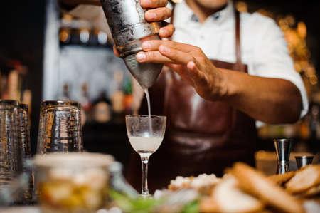 barman i mixes a white cocktail using bar equipment