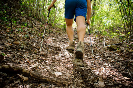 active runner climbs up the mountain using special equipment for Nordic walking and professional shoes