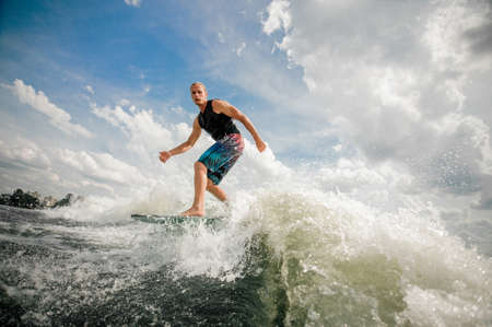 Young athletic rider moves outside of the wake and cuts rapidly in toward the wake