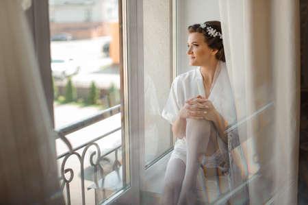 Bruid ochtend voorbereiding. Mooie bruid in witte bruiloft negligé en kousen zitten in de buurt van het grote raam