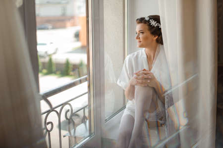 Bride morning preparation. Beautiful bride in white wedding negligee and stockings sitting near the large window Archivio Fotografico