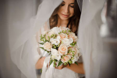 Bride morning preparation. Portrait of a lovely and young bride in a white veil hoding a wedding buquet of flowers