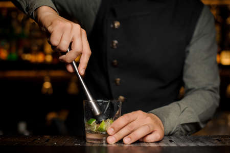Barman squeezing the fresh lime juice making tasty Caipirinha alcoholic cocktail on the bar counter