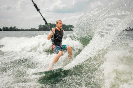 Young athletic man wakesurfing on the board holding a cable