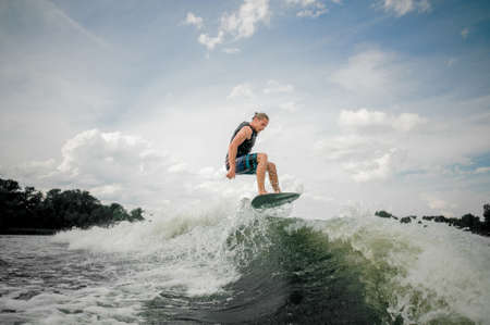 Wakesurf rider jumping on the waves of a river Stock Photo
