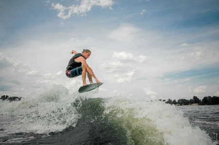 Young wakesurf rider jumping on the waves of the river Stock Photo