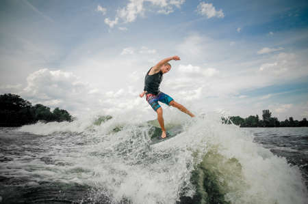 Athletic guy wakesurfing on the board down the river against the sky Stock Photo