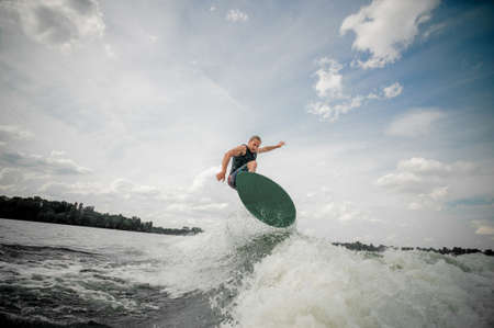 Young and active man wakesurfing on the board Stock Photo