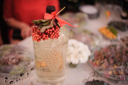 crystal bottle decorated with a branch of red viburnum stands on a festive table amid snacks