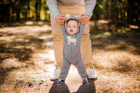 Man walking with a cute smiling baby boy in beautiful park on the bright day