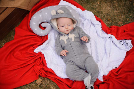 Sweet little baby dressed in romper with hood lying on the pillow in the park