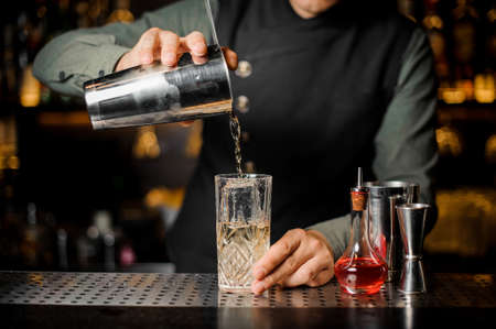 Professional bartender filling a fresh cocktail into the glass shom the shaker at the steel bar counter