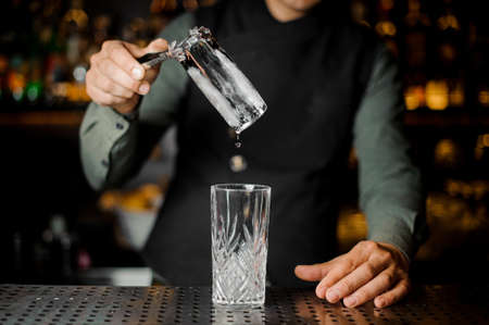 Bartender putting a big ice cube into an empty glass on the steel gray bar counter close-up Stock Photo