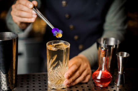 Professional bartender making final preparing of the fresh cocktail in the glass with the violet flower