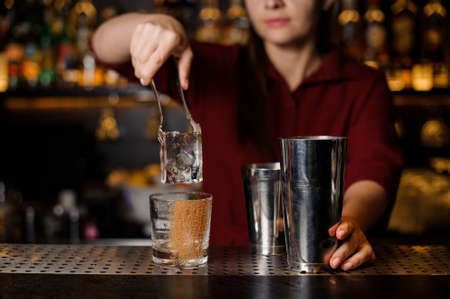 Barmen girl putting with a tongs a big ice cube into an empty glass on the steel bar counter Stock Photo