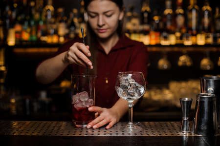 Professional bartender girl stiring an adorable light red cocktail in the glass at the steel bar counter