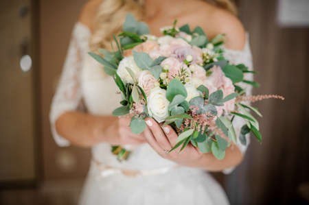 Bride in a white dress holding a beautiful bouquet of wedding flowers made of tender roses