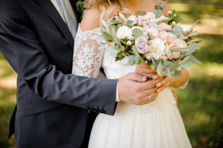 Close up photo of a bridegroom embracing a bride holding a beautiful bouquet of flowers on the background of green lawn