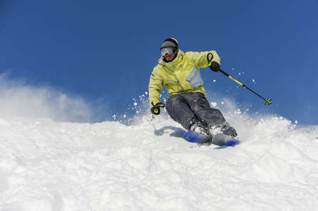Skier dressed in yellow and grey sportswear running down the mountain slope on the background of amazing resort Gudauri, Georgia