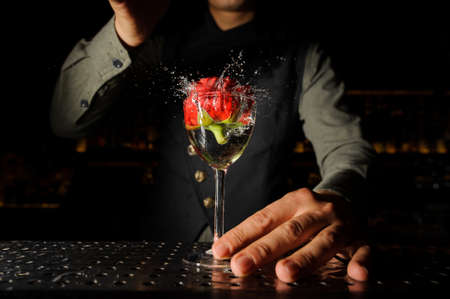 Elegant cocktail glass with splashing alcoholic drink and rose in it in a barman hand on the bar counter Foto de archivo