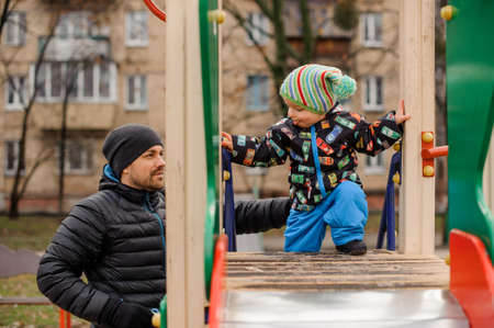 Cute toddler boy playing with father on the playground in the yard on the autumn day Stock Photo