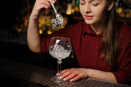 Beautiful female barman putting ice cubes into a glass making a fresh and tasty Aperol syringe cocktail Stock Photo